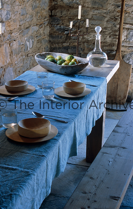 The refectory table is covered in a simple blue table cloth and is laid with wooden plates and bowls