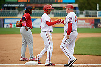 Harrisburg Senators left fielder Juan Soto (10) first bumps with manager Matthew LeCroy (24) as he stands on third base in front of Vladimir Guerrero Jr. (27) during the first game of a doubleheader against the New Hampshire Fisher Cats on May 13, 2018 at FNB Field in Harrisburg, Pennsylvania.  New Hampshire defeated Harrisburg 6-1.  (Mike Janes/Four Seam Images)