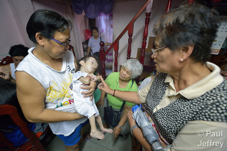 Iluminada Castillo holds her 3-year old grandson Ceyrus in his home in the Malate neighbohood of Manila, during a visit by several members of Kaisahan ng Magulang at Anak na Maykapansanan (Kaisaka), a mothers' group that carries out community based rehabilitation with families which have members with disabilities.