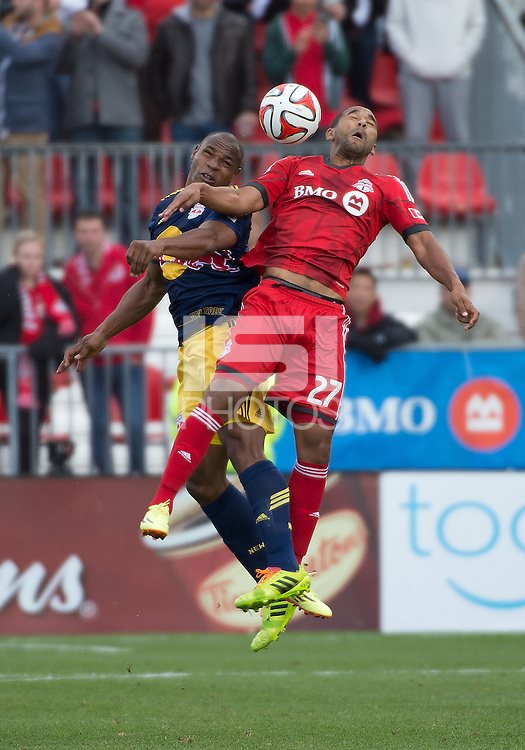 Toronto, Ontario - May 17, 2014: Toronto FC forward Luke Moore #27 jumps for a ball with New York Red Bulls defender Jamison Olave #4 in the second half during a game between the New York Red Bulls and Toronto FC at BMO Field. Toronto FC won 2-0.