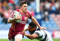 PICTURE BY VAUGHN RIDLEY/SWPIX.COM - Rugby League - Super League - Huddersfield Giants v Hull FC - Galpharm Stadium, Huddersfield, England - 09/04/12 - Huddersfield's Danny Brough is tackled by Hull FC's Willie Manu.