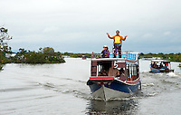 Singing in the rain, a man is on te roof of a boat on the Tonle Sap and singing. Cambodia