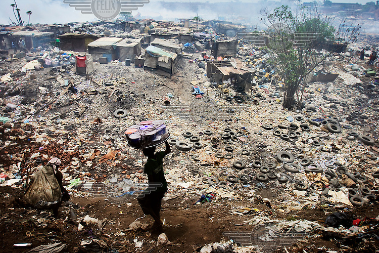 A vendor carrying food on his head descends on a village at the Olusosun landfill site. The Olusosun dump is Nigeria's largest trash heap comprising over 100 acres of garbage and is believed to be the largest in Africa. There are around a thousand houses built within its boundaries.