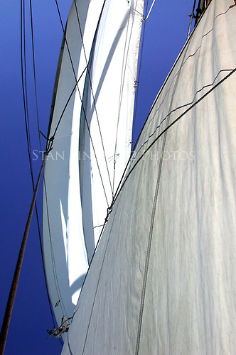 The sailboat is driven by the wind as shown by the sails drawing the wind.  Jib sails are shown in contrast to bright blue skys.