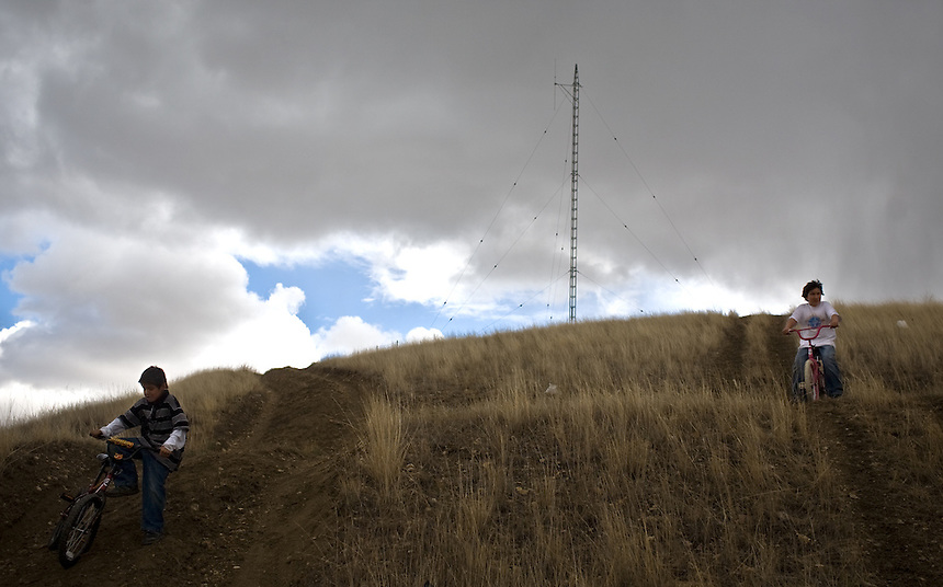 Two kids ride bikes down the hill from the only radio tower on the Crow Indian Reservation in Crow Agency, MT. There are little boundaries on the reservation that separate children from potentially harmful situations.