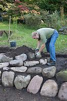 Anlage einer Kräuterspirale im Garten aus Feldsteinen, Kräuter, Feldsteine werden verarbeitet