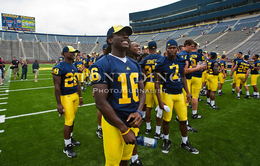 Michigan quarterback Denard Robinson (16) waits for a team photo with teammates on the Michigan Stadium turf, at the annual NCAA college football media day, Sunday, Aug. 22, 2010, in Ann Arbor, Mich. (AP Photo/Tony Ding)