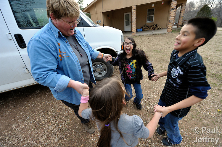 Debbie Humphrey, a United Methodist deaconess, is program director for the Cookson Hills Center, a ministry of The United Methodist Church in Cookson, Oklahoma. Humphrey coordinates work with children. Here she greets children in a rural community where she weekly delivers supplementary food for poor children.