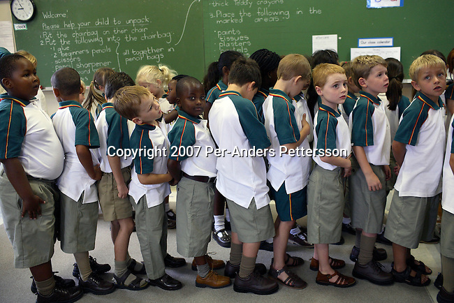 CAMPS BAY, SOUTH AFRICA January 17: Children line up as they attend Grade 1 first day of school at Camps Bay Preparatory School on January 17, 2007 in Camps Bay, an affluent suburb of Cape Town, South Africa. The seaside suburb is one of the most affluent in the country and the school has a good record racial mix..(Photo by Per-Anders Pettersson/Getty Images)...