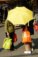 Two Chinese women chatting under a yellow parasol, Chinatown, Vancouver, British Columbia, Canada