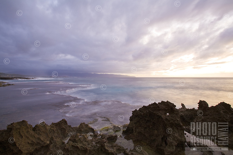 Slow motion image of waves breaking over the rock shelf at Shark's Cove, with Kaena Point in the background