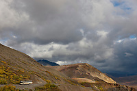 A tour bus on the Denali park road takes visitors along the precipitous ridge of Polychrome pass in Denali National Park.