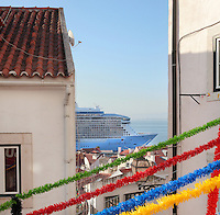 Colourful fiesta streamers in Alfama, the oldest district in the city and the original Moorish area, with the cruise ship Anthem of the Seas on the river Tagus estuary behind, Lisbon, Portugal. Picture by Manuel Cohen