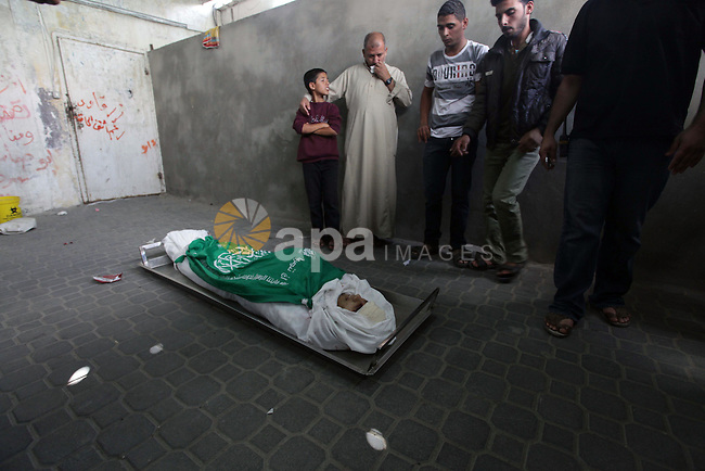 Relatives of Palestinian Hamas militant Rabee Baraka gather arround his body in a hospital in Khan Younis in the southern Gaza Strip November 1, 2013. The local commanders of Hamas's military wing were killed by tank fire, Palestinian officials said, while the Israeli army said five of its soldiers were wounded by an explosive device. The Israeli military said the fighting erupted when an explosive device went off as troops were clearing a tunnel from the Gaza Strip into Israel, allegedly to be used as a springboard for militant attacks. Photo by Ashraf Amra