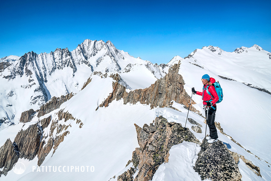 A woman ski tourer stands on the Hubelhorn looking out at the Bernese Oberland, including the Schreckhorn and Lauteraarhorn, while on the Berner Haute Route, Switzerland