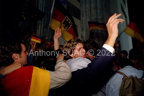 Berlin, Germany<br /> October 3, 1990<br /> <br /> Crowds of East and West Germans gathered at the Brandenburg Gate to drink, wave the West German flag and celebrate the reunification of East and West Germany, nearly one year after the Berlin Wall was opened allowing East Germans to travel freely to the West. By October 1990 almost nothing remained of the wall.
