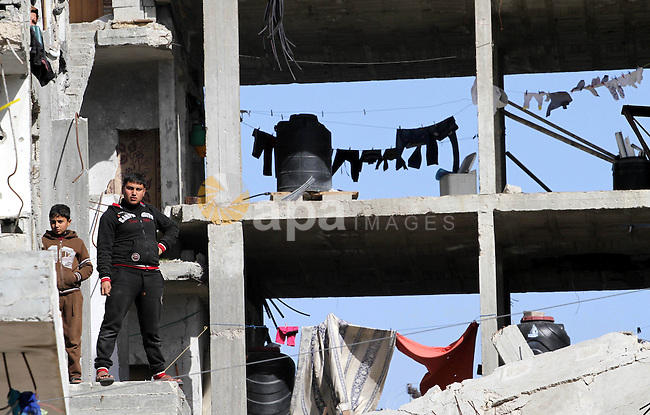 Palestinian children look on from their damaged house during a protest against the United Nations decision to suspend payments for Palestinians, whose houses were damaged during a 50-day war last summer, in Beit Hanoun in the northern Gaza Strip January 30, 2015. The main U.N. aid agency in the Gaza Strip said on Tuesday a lack of international funding had forced it to suspend payments to tens of thousands of Palestinians for repairs to homes damaged in last summer's war. Photo by Mohammed Asad