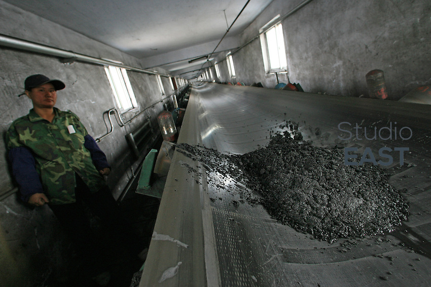 A worker checks the transportation of coal on a conveyor belt out of Lingxin mine, part of Shenhua group, near Yinchuan, Ningxia province, China, on July 11, 2006. China Shenhua Energy is planning the world's biggest share sale by a coal mining company, hoping to raise as much as $6.3 billion to expand pits and delivery networks as demand for the fuel surges. Photo by Servais Mont/Pictobank