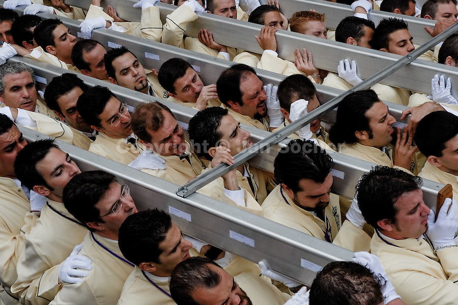 About 250 Spanish men, the brotherhood members, carry a large heavy throne (which may weigh over 5.000 kilograms) during the Holy Week celebration in Malaga, Spain, 2 April 2007.