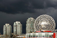 Telus World of Science dome and condominium towers against dark clouds, Vancouver, BC, Canada