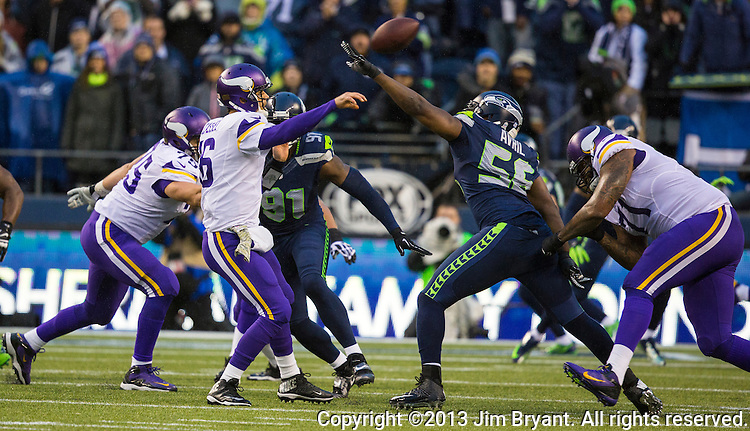 Minnesota Vikings quarterback Matt Cassel passes under pressure from Seattle Seahawks linebacker Cliff Avril (56)  at CenturyLink Field in Seattle, Washington on  November 17, 2013.  The Seahawks beat the Vikings 41-20.  ©2013.  Jim Bryant. All Rights Reserved.