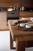 Fresh goats cheese and a sliced loaf of bread have been prepared on the kitchen table