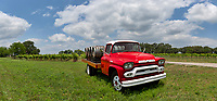 Hill Country panorama of a winery with this bright red truck with wine barrels on it at a winery near Kerrville. The truck sits in front of the grapes vines that have been planted on this landscape on this beautiful day with nice blue sky and puffy clouds in the Texas Hill Country.