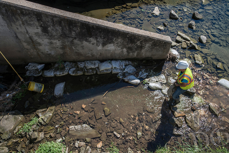 NWA Democrat-Gazette/ANTHONY REYES &bull; @NWATONYR<br /> Eion Garza, with JLA Construction of Springfield, Mo., hauls sandbags Friday, Sept. 2, 2016 to a waiting bucket to be hauled out of Spring Creek in Springdale. The section of the creek lead to the construction area for Walter Turnbow Park in Shiloh Square.