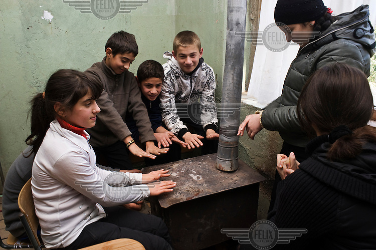 Children gather round the stove to keep warm in their classroom during their break at school.