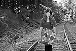 A beautiful gypsy clown girl standing on the train tracks