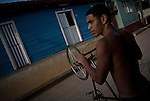A boy with his bike in a street in Baracoa.