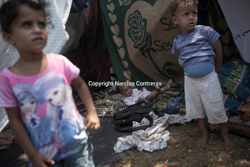 "In this Friday, Aug. 15, 2014 photo, Palestinian children stand outside a tent in a temporary shelter set up around Al-Shifa hospital as their home remains in ruins after it was completely destroyed during the ""Protective Edge"" Israeli military operation in Shuyaja neighborhood in Gaza City Strip. (Photo/Narciso Contreras)"