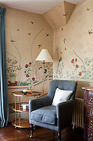 A corner of a bedroom decorated with vintage wallpaper depicting a garden scene. A floor lamp stands behind a blue upholstered armchair