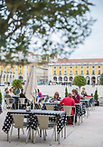 PORTUGAL, Lisbon, People are dining outdoors in Praca do Comercio, Yellow Buildings in the background