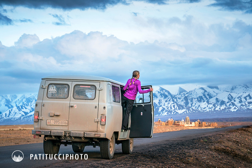 A woman leans out of a UAZ 452, a Russian made bus, while on a road trip through Kyrgyzstan