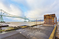 Empty pallets await cargo on dock. Astoria-Megler Bridge, Columbia River, a steel girder continuous truss bridge spanning the Columbia River between Astoria, Oregon and Point Ellice, Megler, Washington, United States.  Total span 14 miles.  It is the longest continuous bridge in North America.