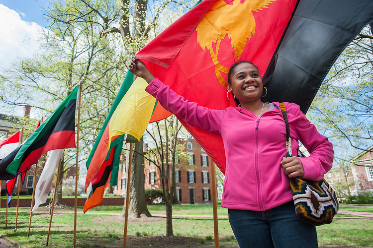 Mary Fairio of Paupa New Guinea poses with her countries flag on college green as her friend snaps a photo. Photo by Ross Brinkehroff.