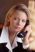 A business woman on the telephone with a concerned expression.