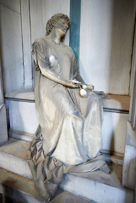 Picture and image of the Neo Gothic Erba stone tomb sculpture of a female figure, with her eyes closed and some poppy seeds in her hands, which are a pagan symbol with a funeral meaning because of their narcotic properties. The garment, stretching along her arm, leaves one shoulder undressed, thus giving the sleeper a touch of sensuality that did not fail to arouse some controversy among the contemporaries. By Sculptor Sculptor S. Saccomanno 1883.  Section A, no 50, The monumental tombs of the Staglieno Monumental Cemetery, Genoa, Italy