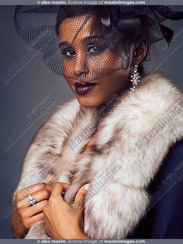 Beauty portrait of a smiling young black woman wearing fur and black veil covering her face