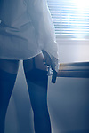 Sensual closeup of a sexy woman standing by the window with a gun in her hand wearing a mens dress shirt and stockings looking out into the night