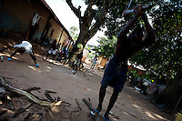 Florentino te', 25 years old, cuts wood in the the front garden of his house while family members play and work around him in a very poor neighborhood in BIssau, Guinea Bissau on Friday September 14 2007.///..Guinea Bissau is infamous for its cocaine trafficking. in 2005 Colombian cartels begun to arrive in the country transforming it into a Narco State. Up to 5 tons of pure cocaine are estimated to be arriving in the country every week. Guinea Bissau is the 5th poorest country in the world, making it the ideal transit base for the cocaine that will finish on the european markets. Corruption and involvement in the trafficking are present at every level of its institutions..Guinea Bissau is only one of the countries in West Africa involved in cocaine trafficking. Tons of Cocaine have been seized in Nigeria, Senegal, Ghana and  Sierra Leone.