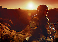A man sits on his motorcycle at sunset while taking a break from riding in the desert of Arizona.
