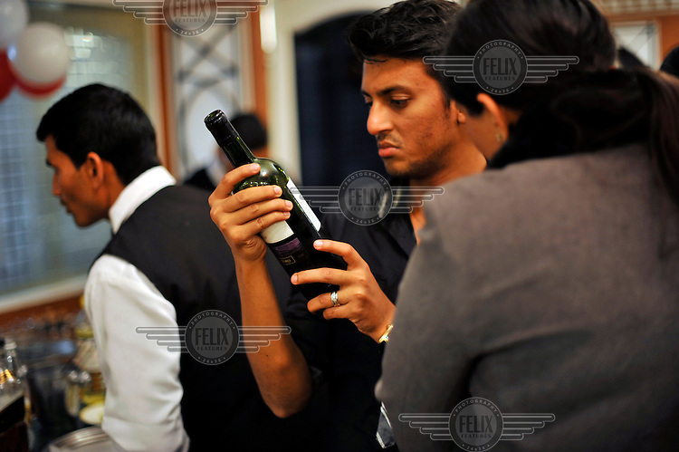 A guest reads the label on a bottle of wine at a wedding reception of British/Punjabi couple Lindsay and Navneet Singh in Amritsar.