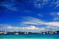 Vessup Bay beach with sailboats at anchor and blue sky & clouds. St Thomas, US Virgin Islands Caribbean.
