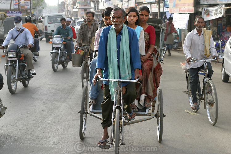 Munna Kailash a rickshaw driver in Varanas, India, ferries his wife, niece, and son on a shopping trip. (From the book What I Eat: Around the World in 80 Diets.) The caloric value of his typical day's worth of food in the month of April was 2400 kcals. He is 45 years old; 5 feet, 6 inches tall; and 106 pounds. India has about 10 million cycle rickshaws, including passenger and cargo pedal carts. Although Munna owns his rickshaw, most rickshaw pullers rent from fleet owners for about $0.60 (USD) per day. A typical puller in a big city earns about $4 to $5 (USD) per day. Although slower than two-cycle smoke-spewing auto-rickshaws, bicycle rickshaws don't pollute the air, and the only heat they add to the atmosphere is from the bodies of their drivers..