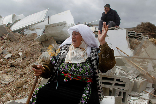 A Palestinian woman sits next on the remains of her home after it was demolished by Israeli bulldozers in a disputed military zone in the area of Musafir Jenbah, which includes several villages, south of the West Bank town of Hebron on February 2, 2016. Israeli forces demolished at least a dozen buildings in a disputed military zone in the southern West Bank, leaving a number of families homeless, authorities and residents said. Israel has carried out a long campaign to relocate the residents of the area, which was declared a military zone by the Israeli government in the 1970s. Photo by Wisam Hashlamoun