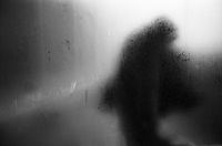 A black silhouette seen behind a frosted window