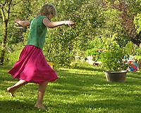 Mädchen, Kind tanzt im Garten voller Lebensfreude