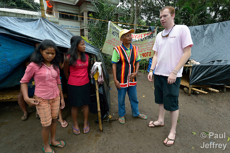 Adam Shaw, a United Methodist mission intern, visits a community of almost 200 indigenous people who fled their village of San Fernando on March 14, 2012, shortly after the March 5 assassination of Jimmy Liguyon, the baranguay captain. Mr. Liguyon was killed by a paramilitary squad led by Aldy Salusad, which was angered by Liguyon's refusal to sign papers ceding the community's land to a large mining company. Convinced they were also in danger from Salusad and his military allies, his widow and other community members fled to the provincial capital of Malaybalay, where they have set up temporary shelters on the grass in front of provincial offices. They promise not to leave until there is justice in the killing of Liguyon. Shaw is assigned to work with INPEACE-Initiatives for Peace in Mindanao..